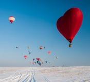 Воздушный шар в форме сердца на поле снега Стоковые Фотографии RF
