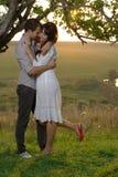 2 возлюбленн целуя под деревом на заходе солнца Стоковая Фотография