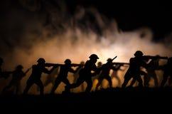 Воинские силуэты солдат против фона темного туманного неба Батальная сцена с взрывом и горящие облака за смоквой Стоковая Фотография RF