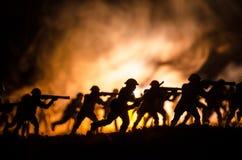 Воинские силуэты солдат против фона темного туманного неба Батальная сцена с взрывом и горящие облака за смоквой Стоковое Изображение