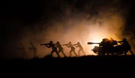 Воинские силуэты солдат против фона темного туманного неба Батальная сцена с взрывом и горящие облака за смоквой Стоковая Фотография