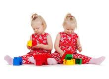 2 двойных девушки в красных платьях играя с блоками Стоковое фото RF
