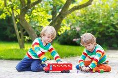 2 двойных мальчика играя с красным школьным автобусом Стоковые Фото