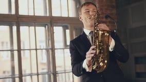 Вокалист джаза в темном платье, составляет для того чтобы выполнить с саксофонистом в костюме на этапе акции видеоматериалы