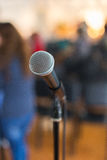 Вокальный микрофон в фокусе против запачканной аудитории на конференции Стоковое Изображение