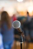 Вокальный микрофон в фокусе против запачканной аудитории на конференции Стоковая Фотография RF