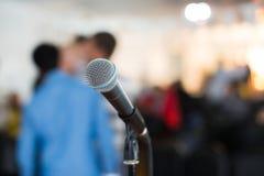 Вокальный микрофон в фокусе против запачканной аудитории на конференции Стоковое фото RF