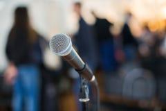Вокальный микрофон в фокусе против запачканной аудитории на конференции Стоковое Изображение RF