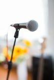 Вокальный микрофон в фокусе против запачканной аудитории на конференции Стоковые Изображения RF