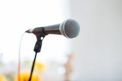 Вокальный микрофон в фокусе против запачканной аудитории на конференции Стоковые Фотографии RF