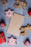 Вокруг малой доски обнаруженные местонахождение сладостные пряник и шарики красного цвета над взглядом Стоковые Фотографии RF