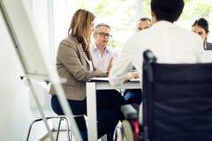 вокруг стола камеры бизнесмена дела имея полагаться смотрящ встречу другие сидя ся команда Стоковое фото RF