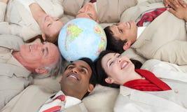 вокруг усмехаться людей глобуса дела лежа Стоковое фото RF