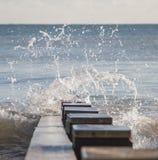Волна брызгая над groyne в заливе Стоковые Изображения