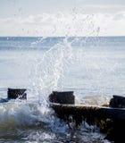 Волна брызгая на groyne на солнечный день Стоковая Фотография