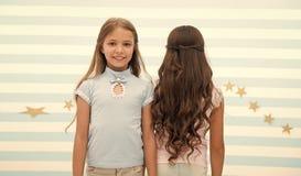 Волна или пермь волос волна или пермь волос для брюнета и белокурой небольшой девушки небольшие дети девушки на парикмахере стопы стоковое изображение