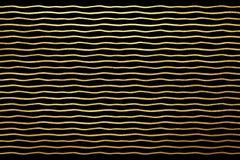 Волнистые блестящие золотые нашивки или предпосылка волн Стоковые Изображения RF