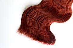 Волнистые красные волосы на изолированной белой предпосылке стоковые фото
