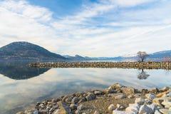Волнорез, горы, и небо отразили в воде спокойного озера с скалистым бечевником стоковая фотография