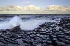 Волны брызгая на камнях на мощёной дорожке гиганта Стоковая Фотография