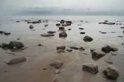 Волны моря брызгая на береге Камни гранита на песчаном пляже Стоковое Изображение RF