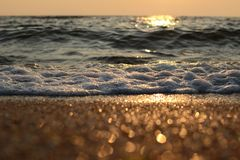 Волны моря и золотой песок на заходе солнца стоковые фото