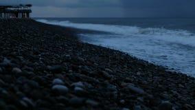 Волны побили на камешки в шторме на море против фона дождевых облаков видеоматериал