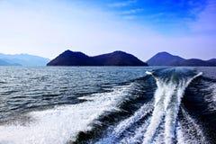 Волны причиненные ветрилом шлюпки на озере стоковое изображение