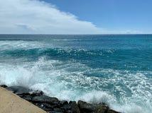 Волны разбивая в утесы на пристани стоковые изображения rf