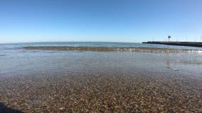 Волны разбивая нежно на тихом песчаном пляже сток-видео