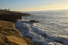 Волны разбивая против скал захода солнца стоковое фото rf