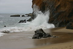 волны скалы разбивая Стоковые Изображения