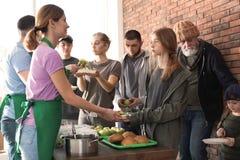 Волонтеры давая еду бедным человекам стоковые изображения rf