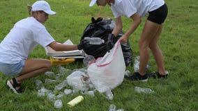 Волонтеры очищая отброс в парке Люди комплектуя вверх пластмассу бутылки на траве сток-видео