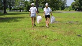 Волонтеры очищая отброс в парке Люди с полиэтиленовыми пакетами полными отброса, загрязнения окружающей среды акции видеоматериалы
