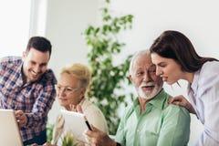 Волонтеры помогают старшим людям на компьютере Молодые люди давая старшее введение людей к интернету стоковое фото