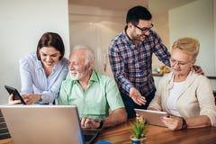 Волонтеры помогают старшим людям на компьютере Молодые люди давая старшее введение людей к интернету стоковое изображение rf