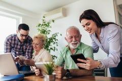 Волонтеры помогают старшим людям на компьютере Молодые люди давая старшее введение людей к интернету стоковая фотография
