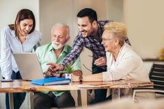 Волонтеры помогают старшим людям на компьютере Молодые люди давая старшее введение людей к интернету стоковое изображение