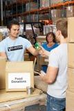 Волонтеры собирая пожертвования еды в пакгаузе стоковые фото
