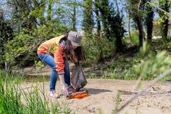 Волонтер женщины комплектует вверх пластиковую бутылку на песочном банке реки r Концепция дня земли стоковое изображение