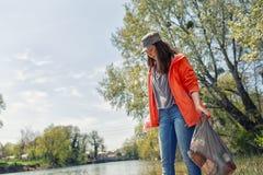 Волонтер женщины на охоте на мусор на реке Деревья и река на заднем плане Концепция охраны окружающей среды стоковые изображения rf