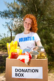 волонтер нося еды пожертвования коробки