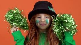 Волосы девушки красные празднуя предпосылку дня ` s St. Patrick оранжевую тряся poms pom акции видеоматериалы
