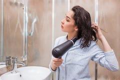 Волосы дуновения женщины суша в ванной комнате стоковое фото