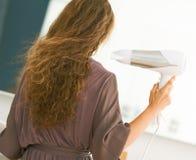 Волосы дуновения молодой женщины суша в ванной комнате Стоковые Фото