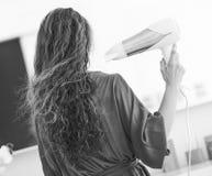 Волосы дуновения молодой женщины суша в ванной комнате Стоковые Фотографии RF