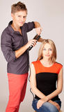Волосы женщины стилизатора утюживя в салоне парикмахера Стоковое Изображение
