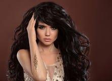 Волосы красоты Красивая девушка модели брюнет с сияющее длинное курчавым Стоковые Фотографии RF