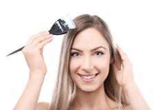 Волосы молодой красивой женщины крася на предпосылке стоковые фото